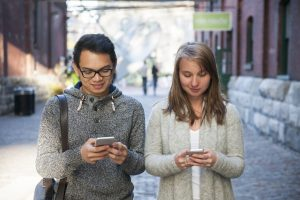 Two young people looking into smartphones while walking on city street