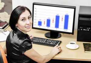 Woman in office with computer smiling