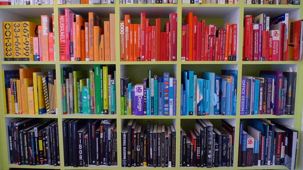 photo of a book shelf with books grouped by color