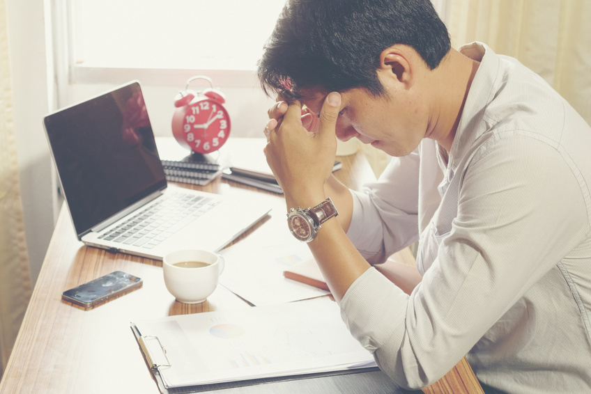 man at desk looking at papers and looking frustrated