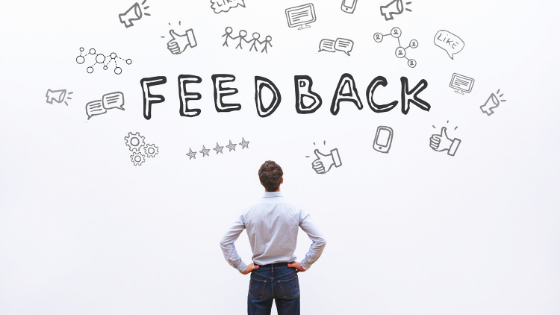 """man standing in front of whiteboard that says """"feedback"""""""