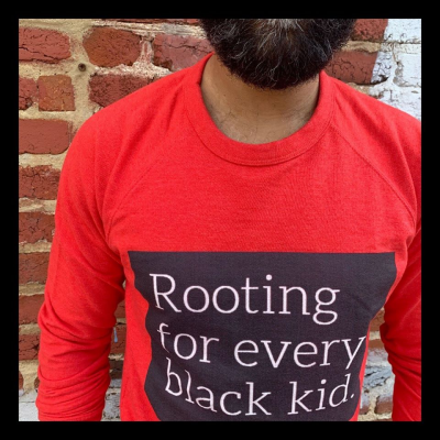 "Man wearing shirt stating ""Rooting for every black kid."""