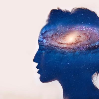 Woman gazing, universe in brain