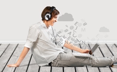 man listening to his headphones and looking at his laptop
