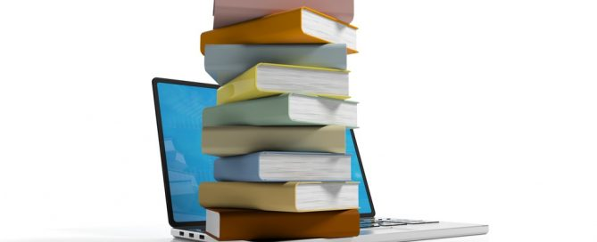 Books stacked on a laptop